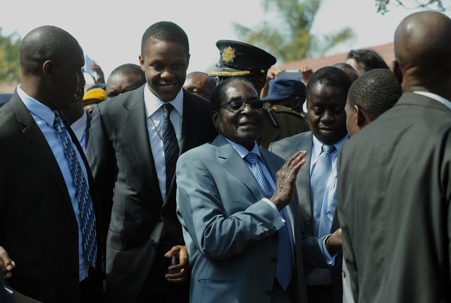 Robert Mugabe, Zimbabwe's president, center, and his son Bellarmine, second left, leaves after voting at a polling station in a school in Harare on July 31, 2013. Photographer: Alexander Joe/AFP/Getty Images