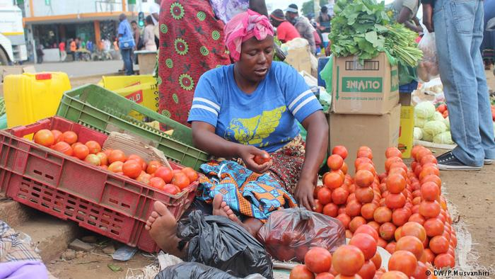 A woman selling tomatoes on a street in Harare