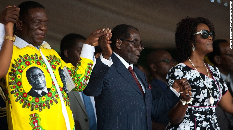 Mugabe holds hands with former Vice President Emmerson Mnangagwa (L) and Grace (R) during his birthday celebrations last year.