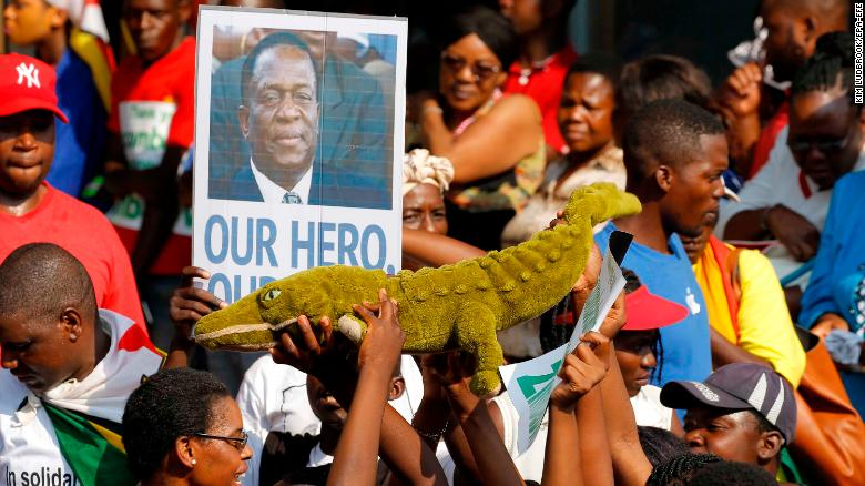 Supporters of Emmerson Mnangagwa hold up a toy to celebrate the man nicknamed 'The Crocodile' as they waited at an airport for his arrival Wednesday.