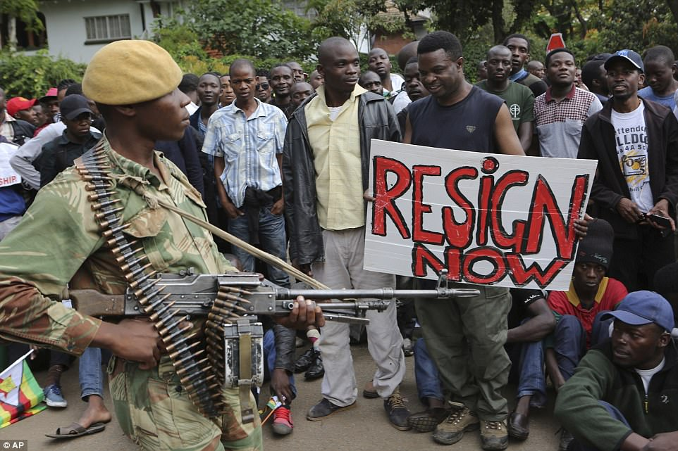 Armed soldiers control a euphoric crowd marching near State House in Harare, demanding the departure of President Robert Mugabe