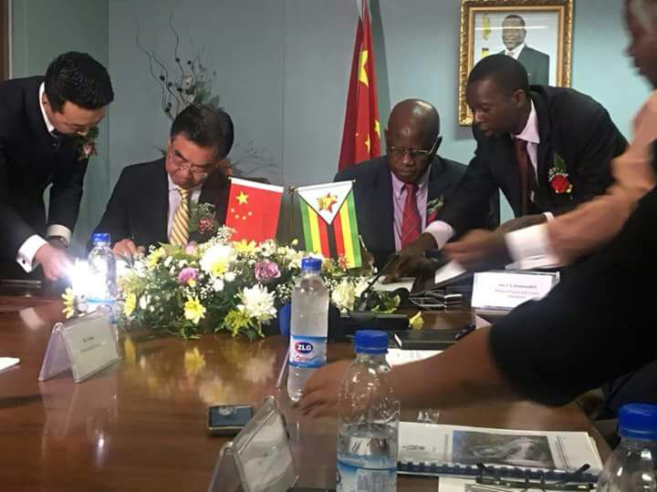 Patrick Chinamasa signs a loan agreement with the Chinese ambassador