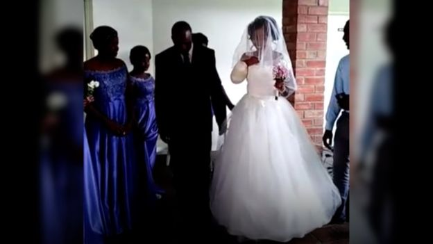 bride entering chapel at her dad's side, with right arm missing and stump bandaged
