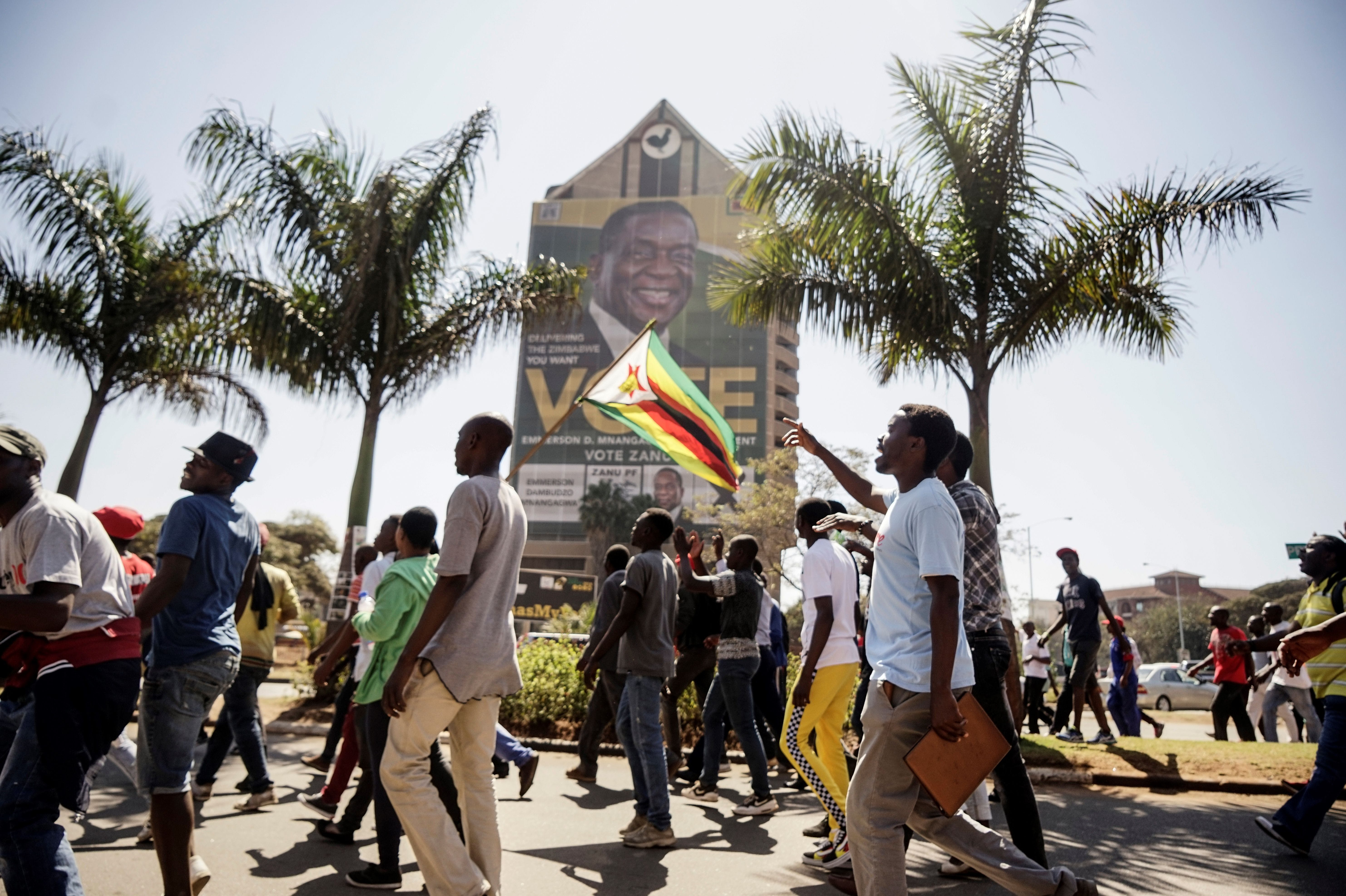 Opposition Movement for Democratic Change (MDC) supporters walk towards the Zimbabwe Electoral Commission (ZEC) headquarters on August 1, 2018 in Harare, to protest against alleged fraud in elections. - Zimbabwe's ruling ZANU-PF party won the most seats in parliament, official results showed on August 1, 2018, as the opposition MDC protested against alleged widespread fraud and the count continued in the key presidential race. (Photo by Zinyange AUNTONY / AFP) (Photo credit should read ZINYANGE AUNTONY/AFP/Getty Images)