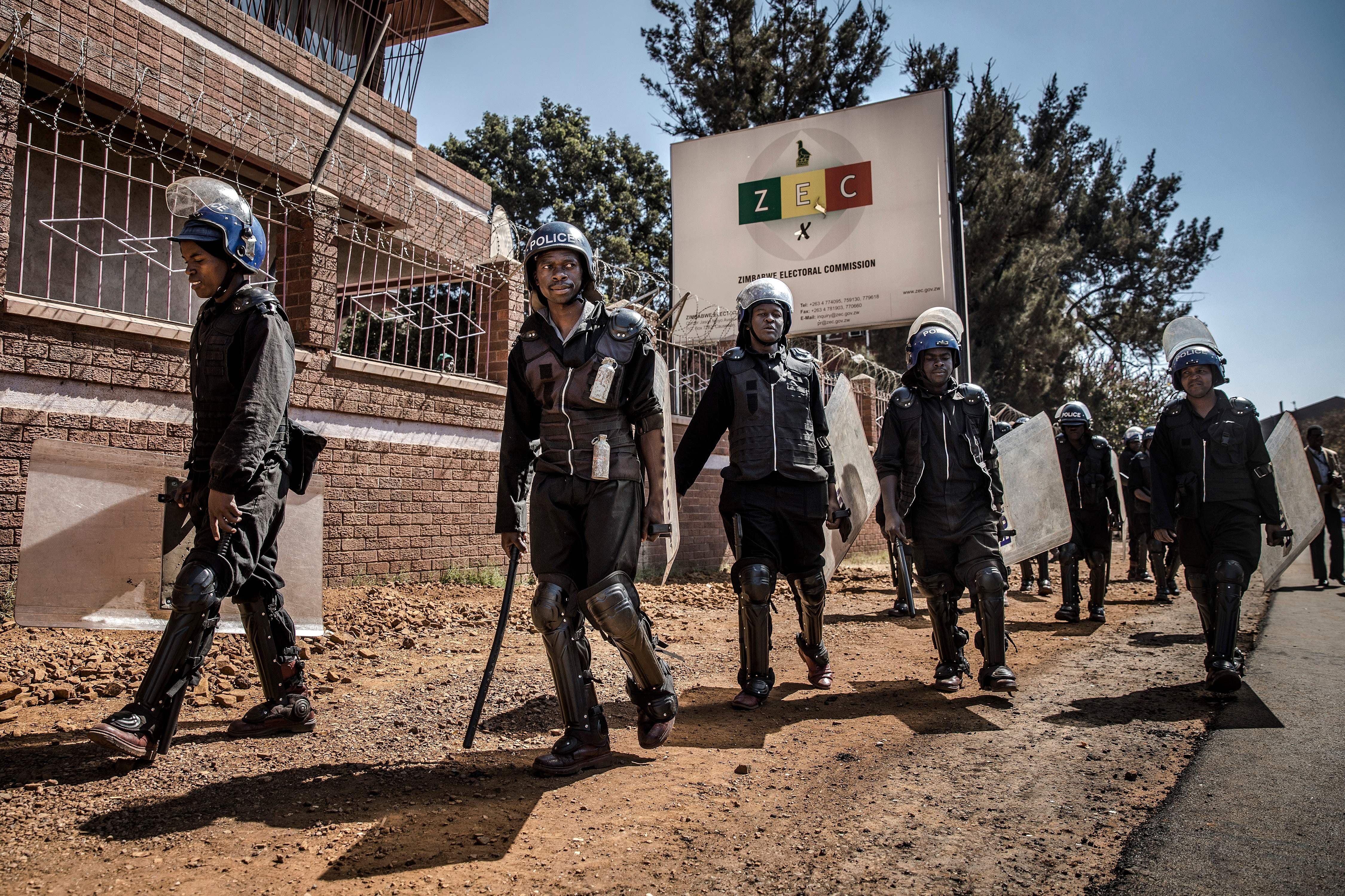 """Zimbabwean anti riot police officers stand guard at the entrance of the Zimbabwe Electoral Commission (ZEC) headquarters in Harare on August 1, 2018, as supporters of the opposition party Movement for Democratic Change (MDC) protest against alleged widespread fraud by the election authority and ruling party, after the announcement of the election's results. - Zimbabwe's ruling ZANU-PF party won the most seats in parliament, official results showed on August 1, 2018, but EU observers criticised the Zimbabwe elections for being held on an """"un-level playing field"""". (Photo by Luis TATO / AFP) (Photo credit should read LUIS TATO/AFP/Getty Images)"""