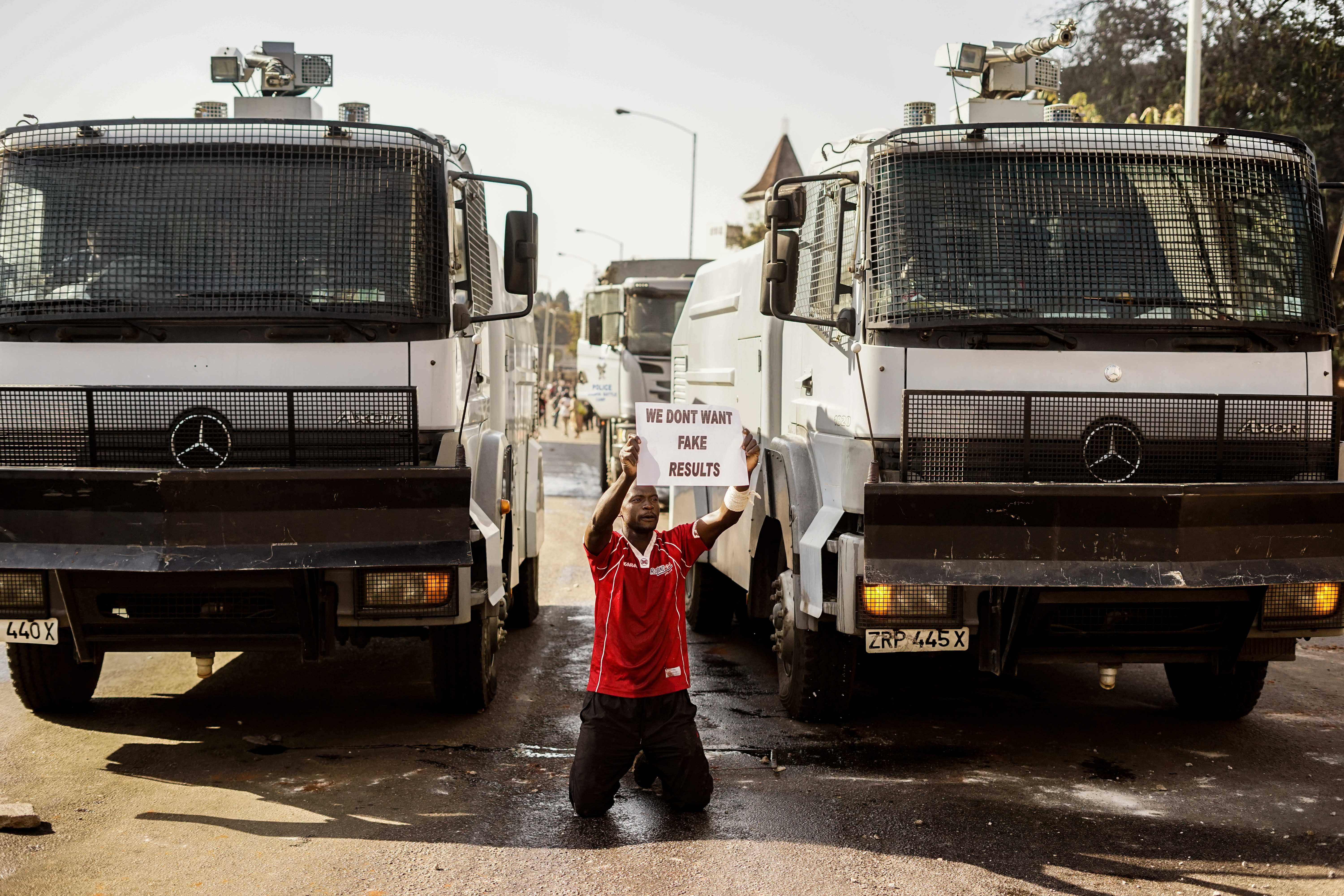 A demonstrator holds a placard as he kneels in front of police water cannons, on August 1 2018, in Harare as protests erupted over alleged fraud in the country's election. - Protests in Zimbabwe's historic elections turned bloody on August 1 as a man was shot dead during demonstrations over alleged vote fraud and the president appealed for calm. The man died after soldiers fired live ammunition during opposition protests in downtown Harare, AFP reporters saw. (Photo by Zinyange AUNTONY / AFP) (Photo credit should read ZINYANGE AUNTONY/AFP/Getty Images)