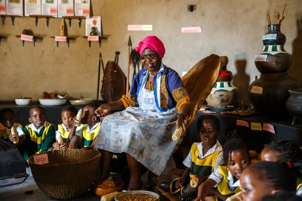 Poet, storyteller and retired schoolteacher, Hatifari Munongi tells a traditional folklore story to a group of kindergarten children visiting the replica traditional homestead she set up in the backyard of her house in Harare October 18, 2018. — AFP pic