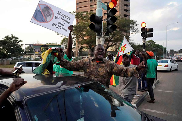 People celebrate in the streets after the resignation of Zimbabwe's president Robert Mugabe in Harare, on November 21, 2017