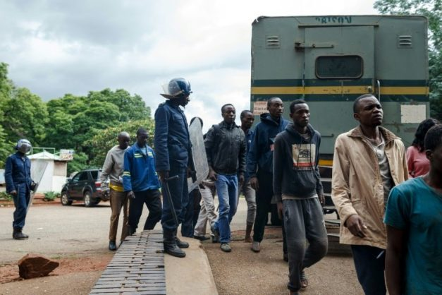 Zimbabwean anti-riot police forces watch men arrested during violent protests triggered by a sudden rise in fuel prices announced by Zimbabwean president, before their hearing at the Law Court in Harare on January 16, 2019. Picture: AFP/File/Jekesai NJIKIZANA