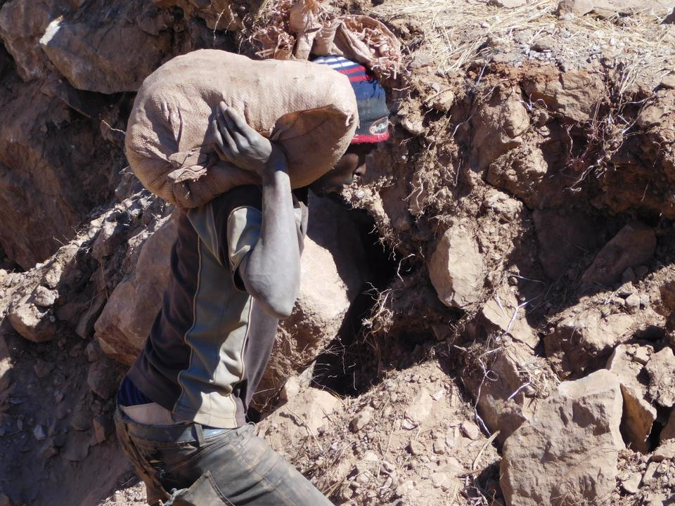 A miner carries a sack of gold ore from a pit at Gaika Mine for panning at a water point.