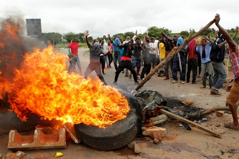Protestors gather near a burning tire in Harare, on Jan. 15.