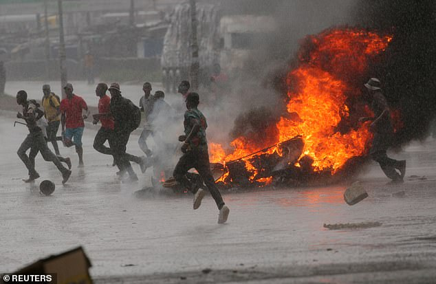 People run at a protest as barricades burn during rainfall in Harare last Monday in protests over the steep rise in fuel prices