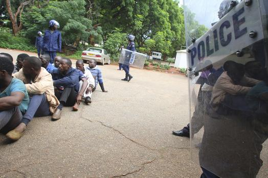 A policeman stands guard as some of the people arrested during demonstrations over the hike in fuel prices, make their court appearance at the magistrates courts in Harare, Zimbabwe, Wednesday, Jan,16, 2019. Some dozens of people appeared in court and were charged with public violence and a human rights group in Zimbabwe says a few people were killed in clashes between demonstrators protesting fuel hikes and security forces who opened fire on some crowds. (AP Photo/Tsvangirayi Mukwazhi)