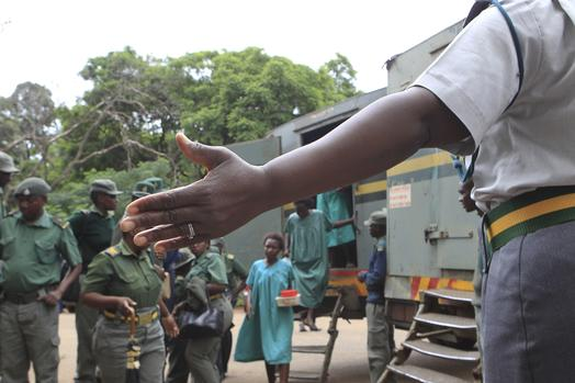 A prison guard directs some of the people arrested during protests over the hike in fuel prices, as they arrive to make their magistrates court appearance in Harare, Zimbabwe, Thursday, Jan, 17, 2019. A Zimbabwe Lawyers for Human Rights says in a statement that pastor and activist Evan Mawarire who is among the more than 600 people arrested this week has been charged with subverting a constittutional government amid a crackdown on protests against a dramatic fuel price increase.(AP Photo/Tsvangirayi Mukwazhi)
