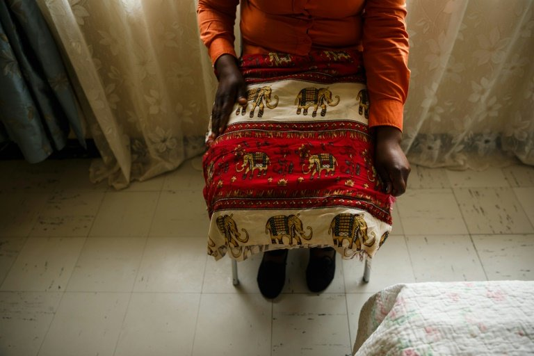 A rape survivor covers her knees and legs with a cloth as she relates how she was abused at her home. AFP/Jekesai NJIKIZANA