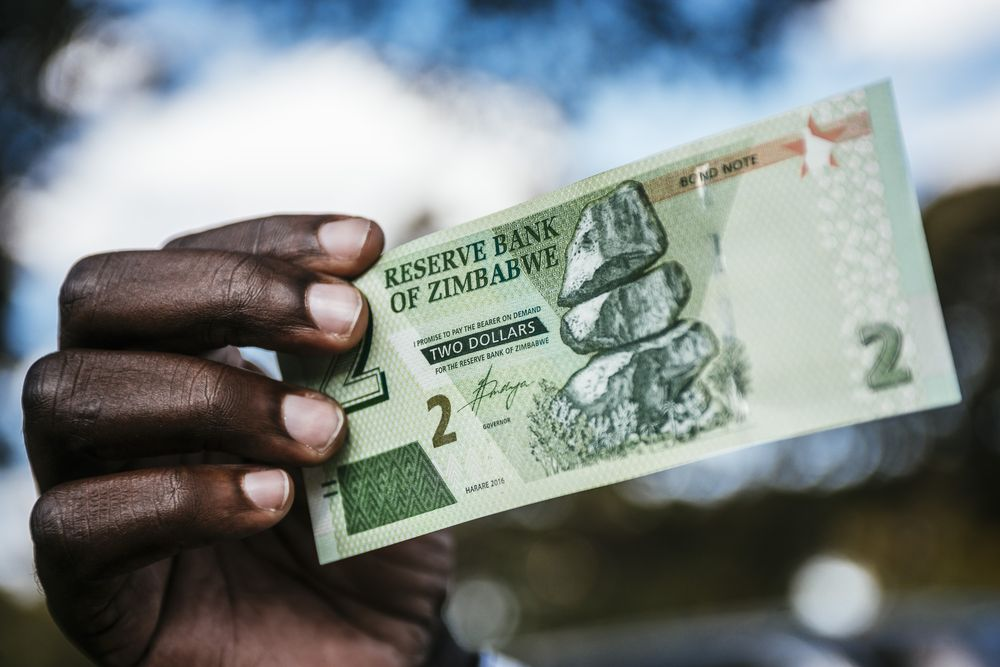 A man holds a Zimbabwean two dollar bond banknote for an arranged photograph in Harare, Zimbabwe.