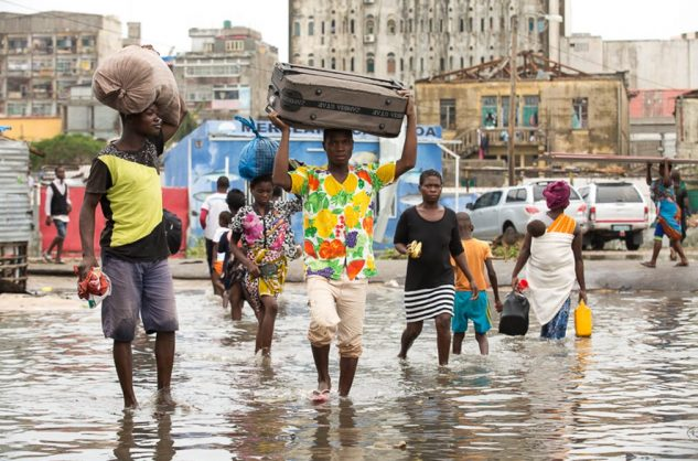 People leaving their homes in the flooded section of Praia Nova, Beira, Mozambique in the wake of tropical cyclone Idai. Denis Onyodi/ IFRC handout