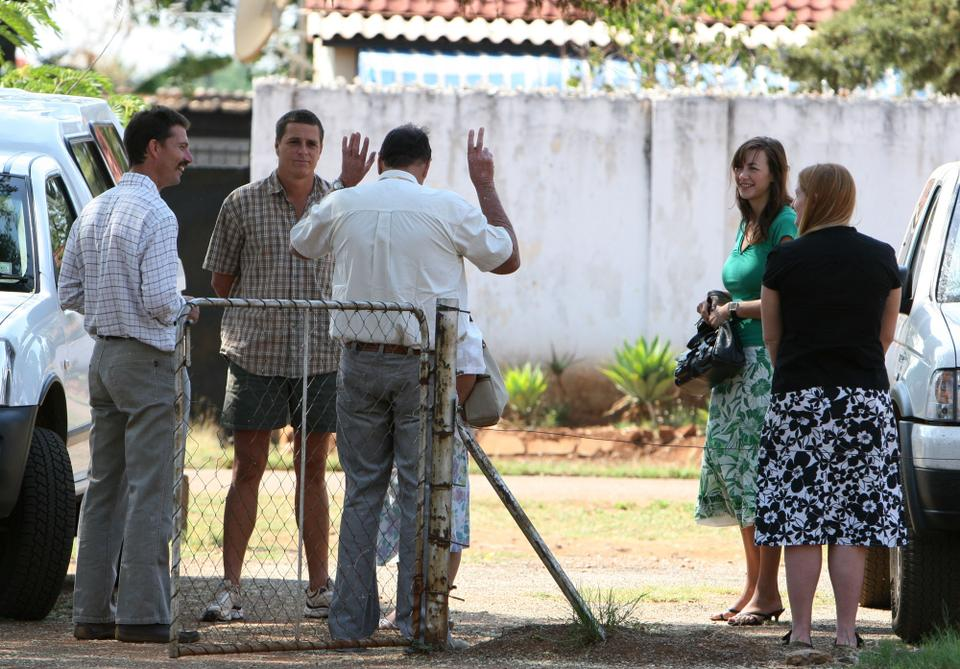 Some of the 11 Zimbabwean white farmers are seen after their court hearing in Chegutu, Zimbabwe Wednesday, Oct. 31, 2007. The farmers were brought to court to answer charges of breaching land laws by defying a government eviction order. The trial date was postponed to a later date.
