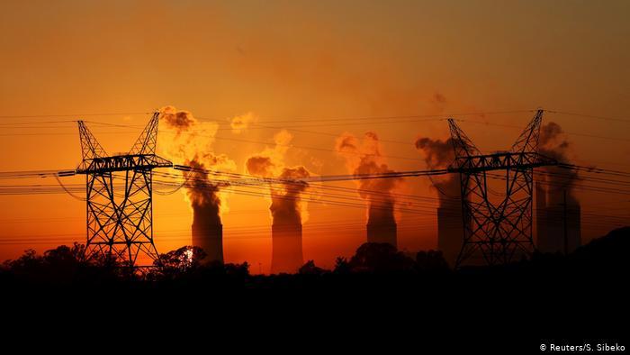 Power masts against an orange sunset