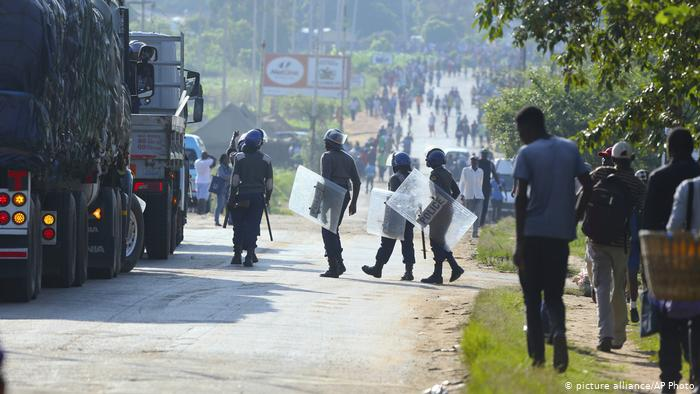 Riot police stand with shields ready