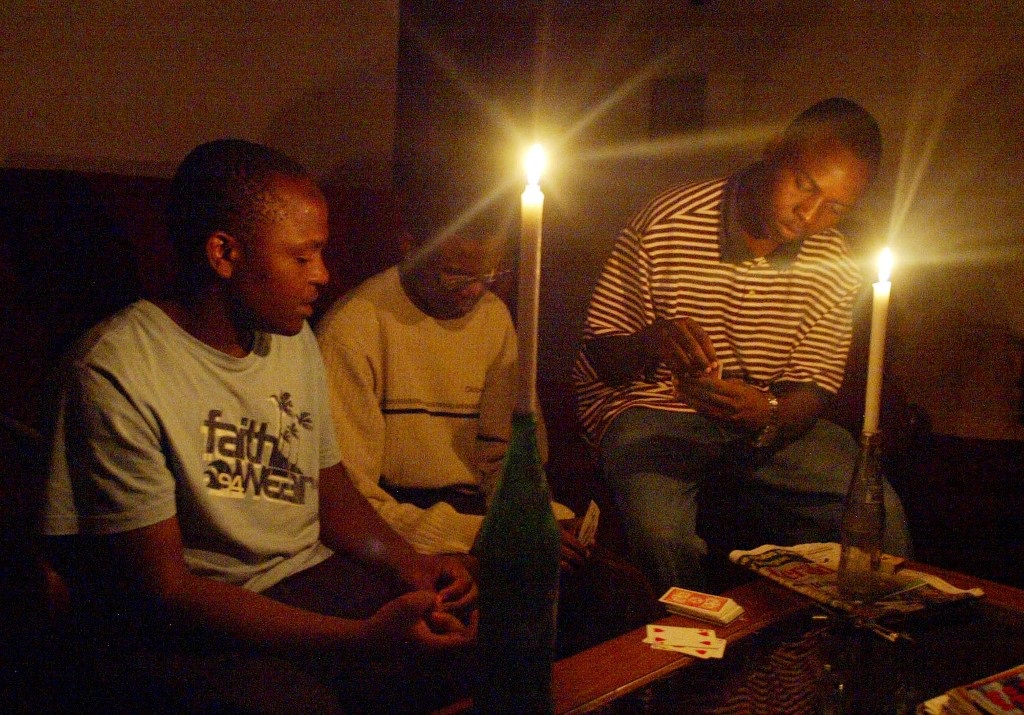 A Zimbabwean family plays card in Harare after the second power cut, which has hit most parts of the country.