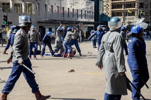 A protester is beaten on the ground by police near Unity Square in Harare on August 16, 2019. Picture: Zinyange Auntony / AFP