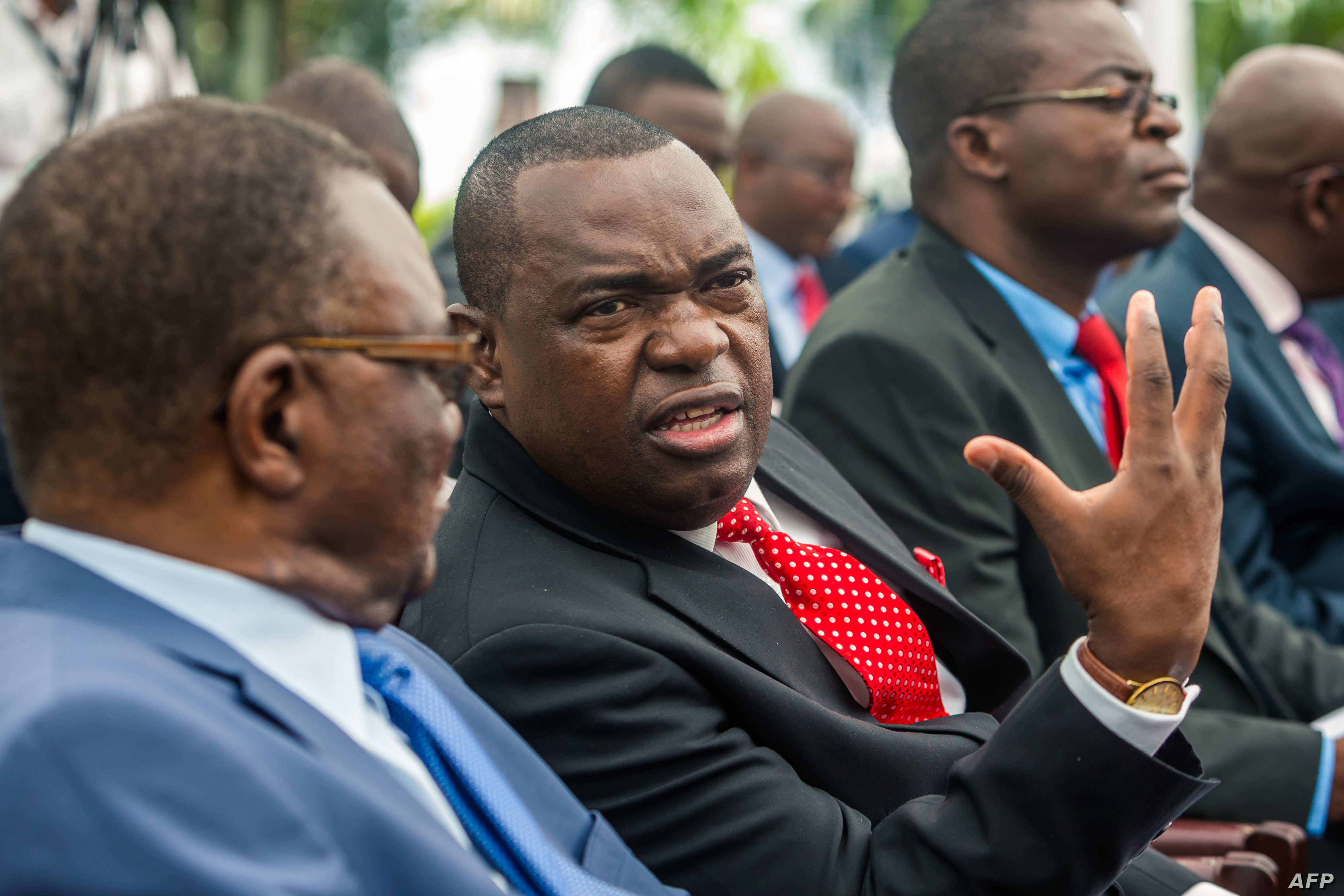 Former Major General Sibusiso Moyo, center, who was appointed Foreign Affairs and International Relations Minister speaks with a fellow minister, before taking the oath of office, Dec. 4, 2017 in Harare.
