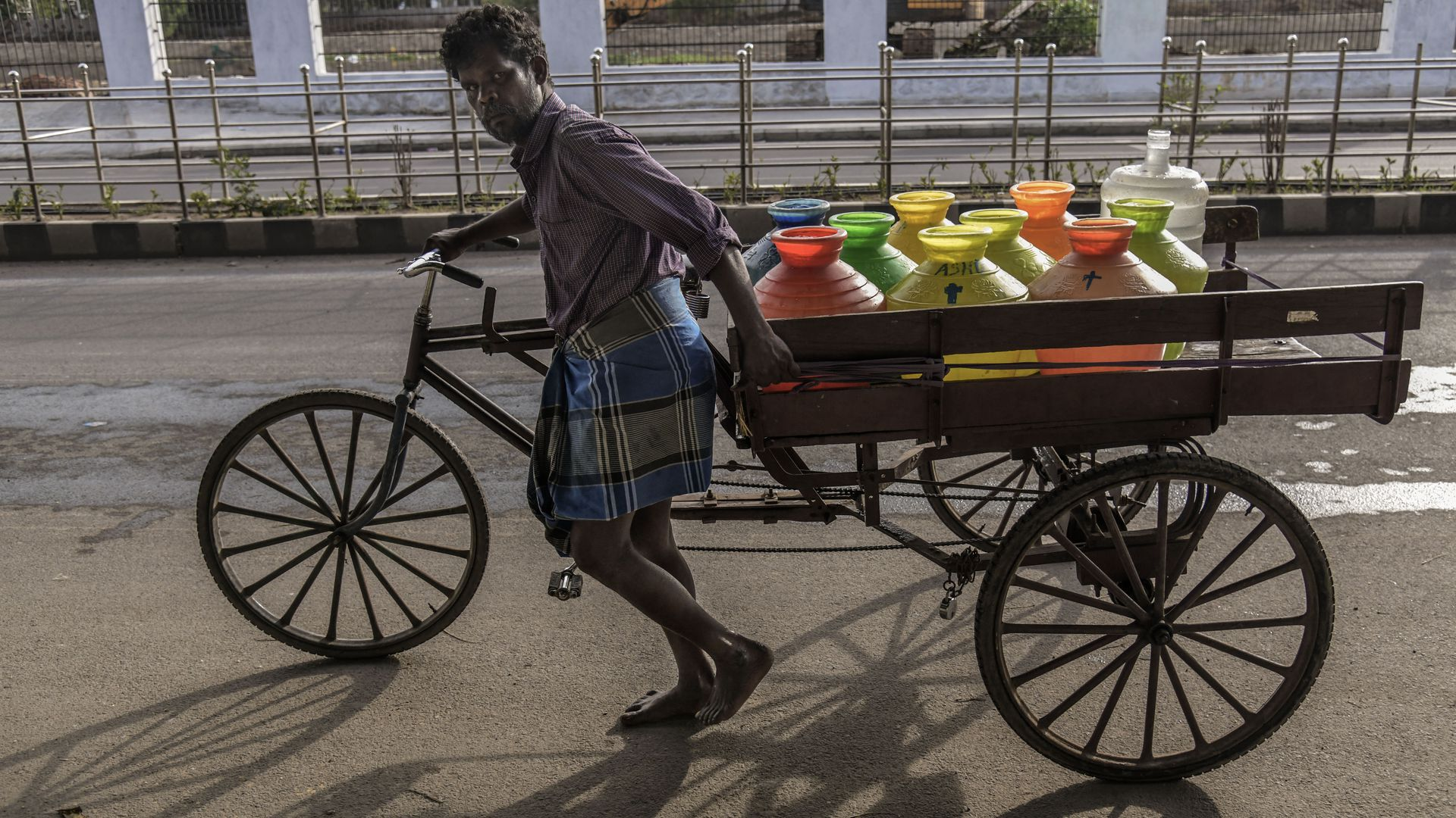 bicyclist transporting colored water cans