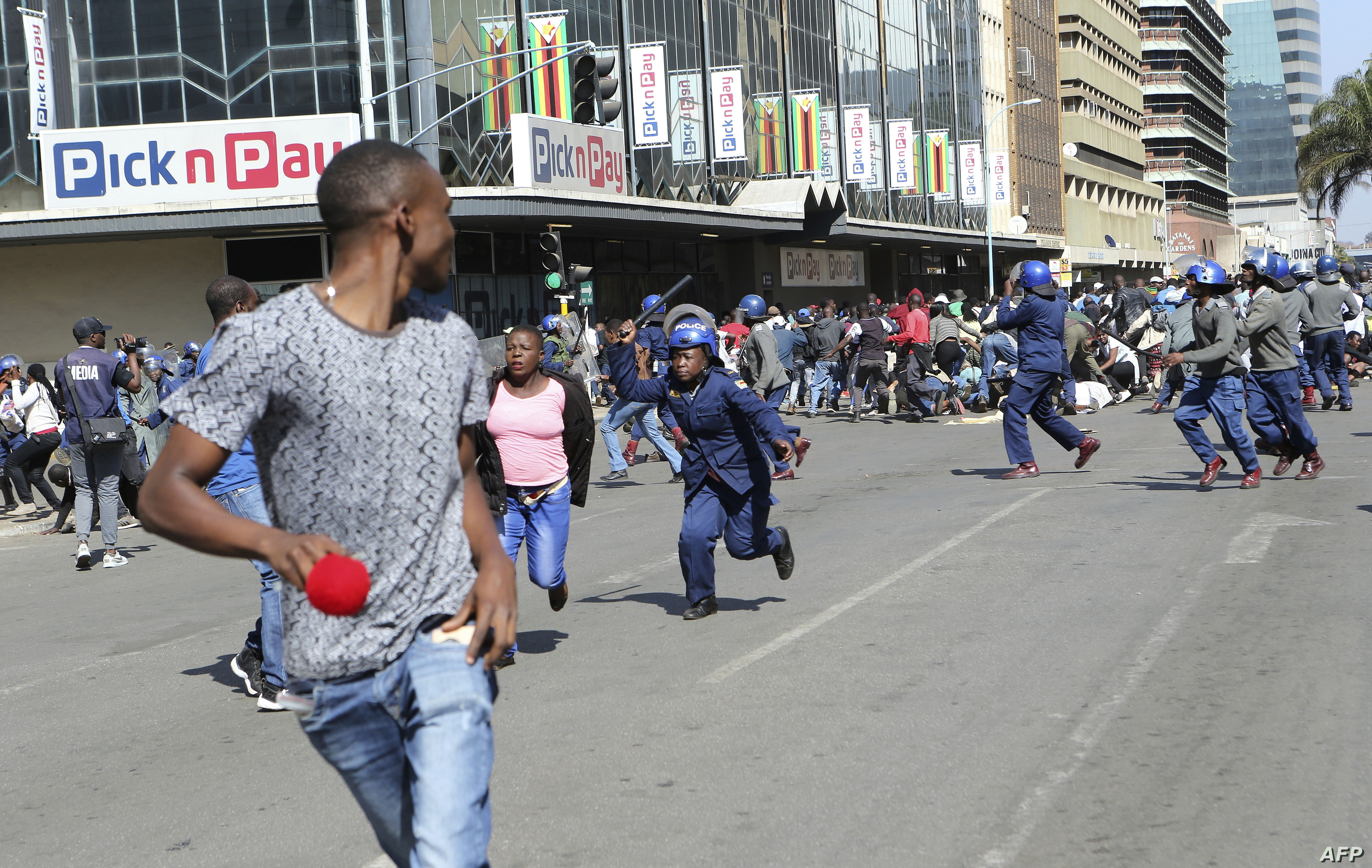 Riot police arrest and forcibly apprehend protestors during protests in Harare, Aug. 16, 2019.