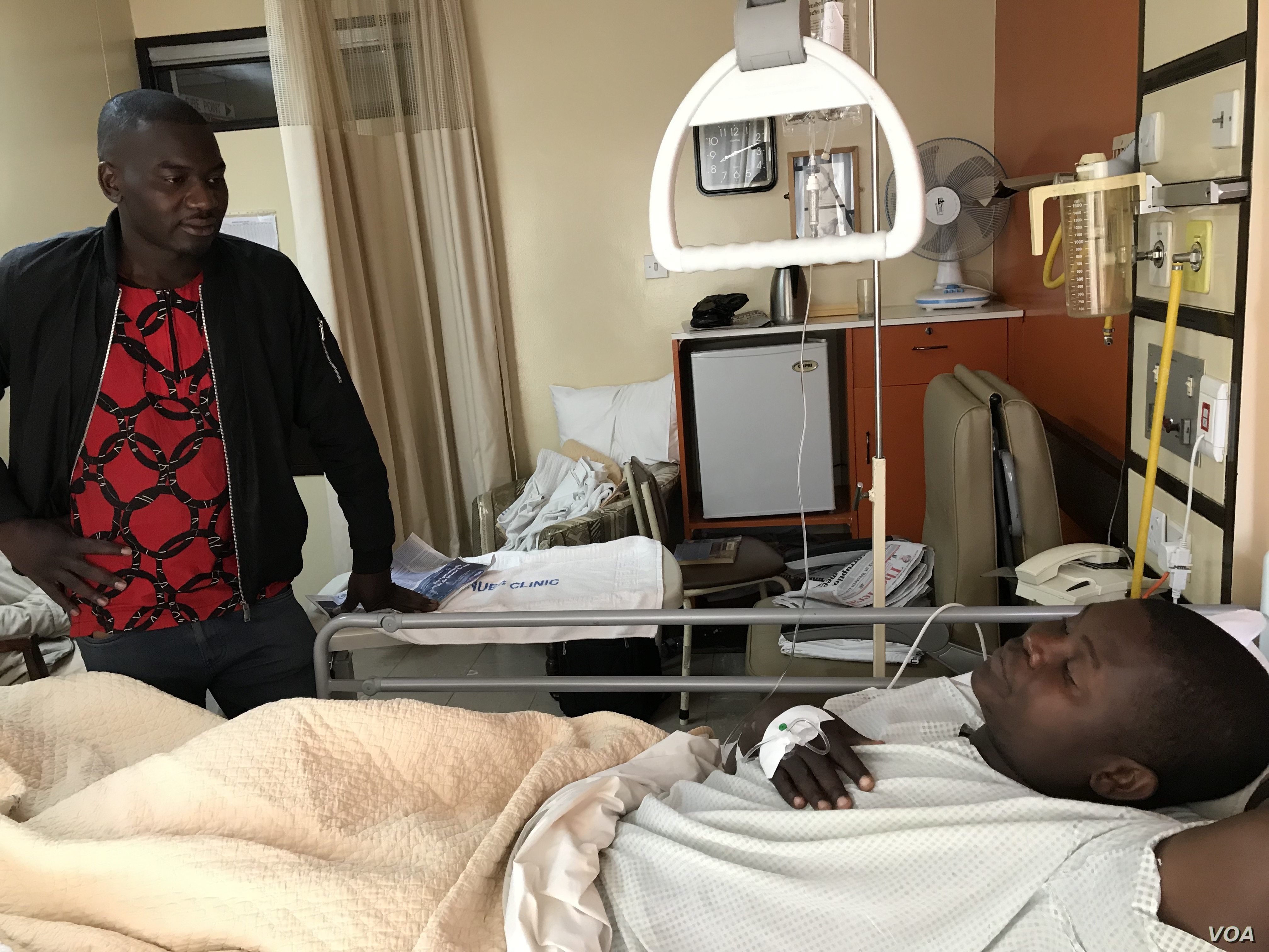 A visitor talks to Tatenda Mombeyarara of Citizens Manifesto in a private hospital in Harare, Aug. 21, 2019. (C. Mavhunga/VOA)