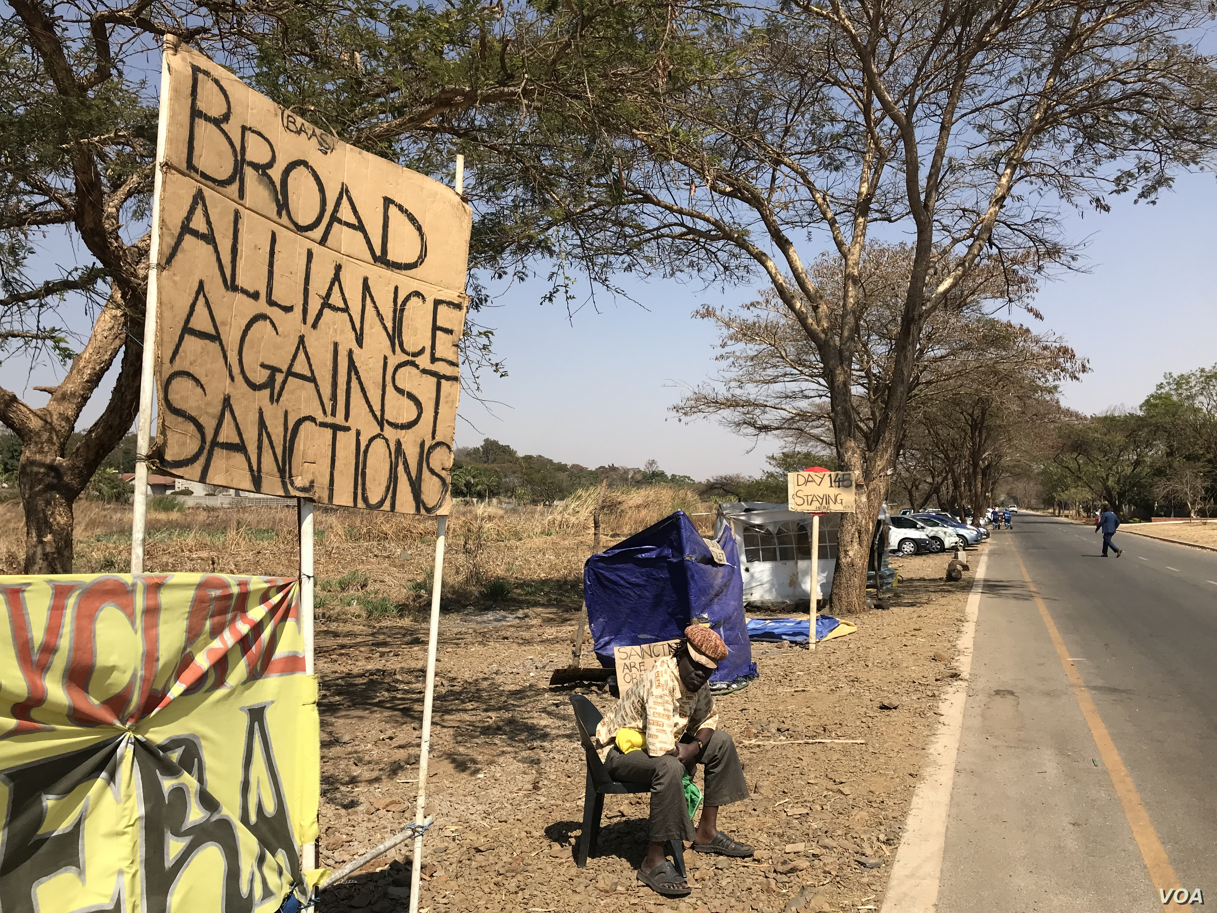 Members of a pro-Zimbabwe government group called Broad Coalition Against Sanctions have been camped outside the U.S. Embassy in Harare, demanding the sanctions be lifted, Aug. 20, 2019. They say sanctions hurt ordinary citizens. (C. Mavhunga/VOA)
