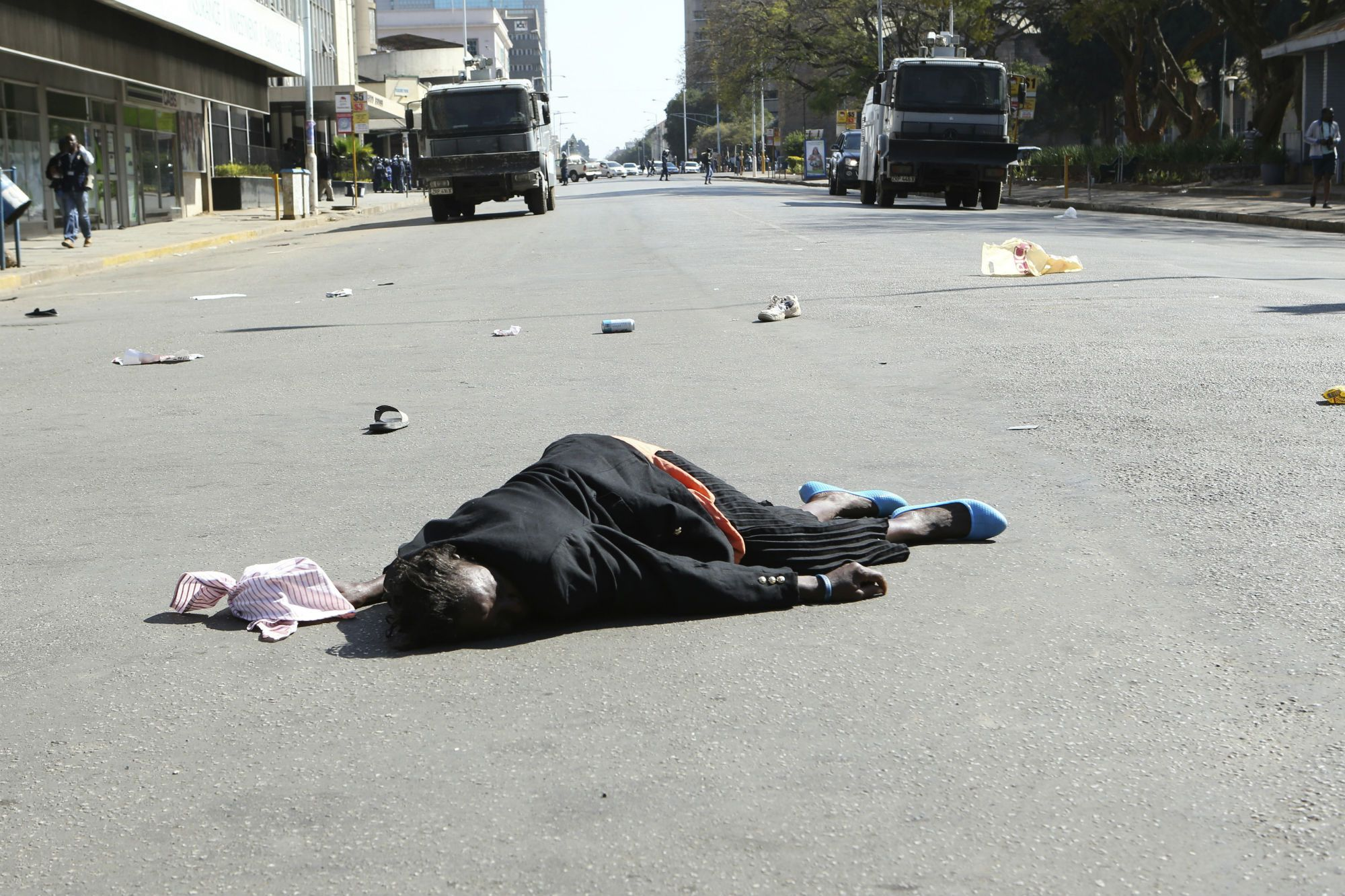 A woman lies injured on the tarmac after been injured during protests in Harare.
