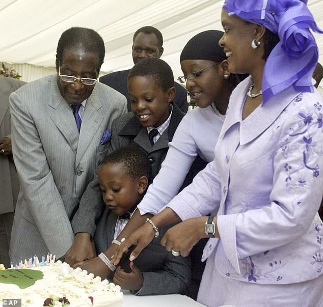 Mugabe cuts his 80th birthday cake helped by his wife Grace, right, his daughter Bona, 2nd right, and his sons Robert Jnr, upper centre, and Chatunga in Kutama in February 2004