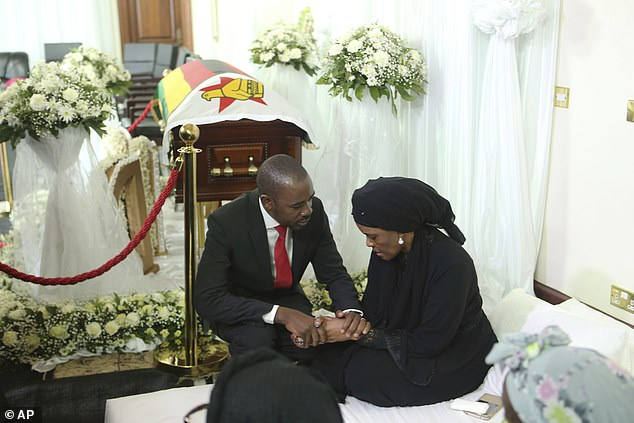 Grace Mugabe, the second wife of Robert Mugabe, is consoled by opposition leader Nelson Chamisa as they sit next to the former Zimbabwean leader's coffin in Harare today