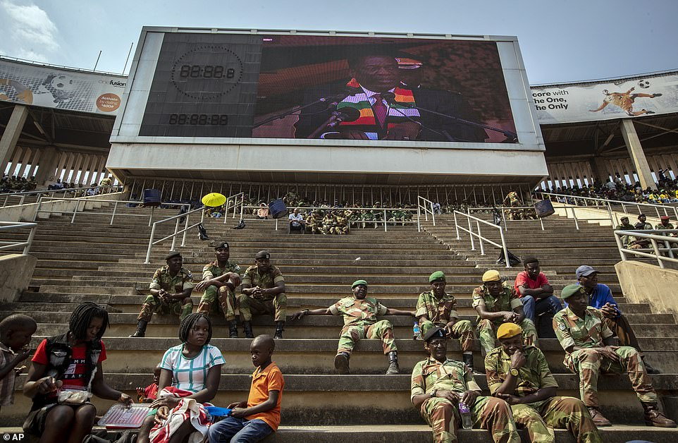 Members of the military sit in the stands as Zimbabwe's President Emmerson Mnangagwa is seen on a video screen above, during the state funeral
