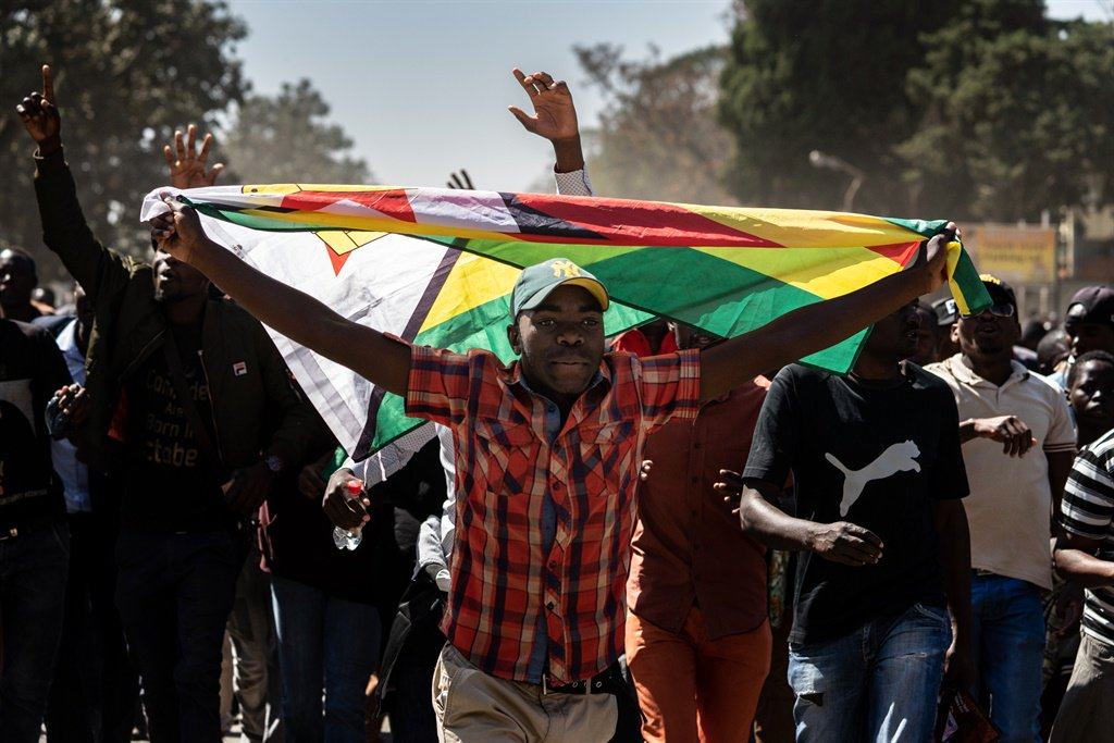A man holding Zimbabwe's national flag walks with