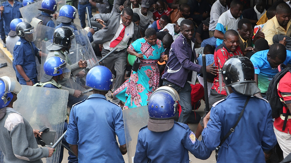 Police surround and assault opposition party supporters who had gathered to hear a speech by the countrys top opposition leader in Harare, Wednesday, Nov, 20, 2019. Zimbabwean police with riot g