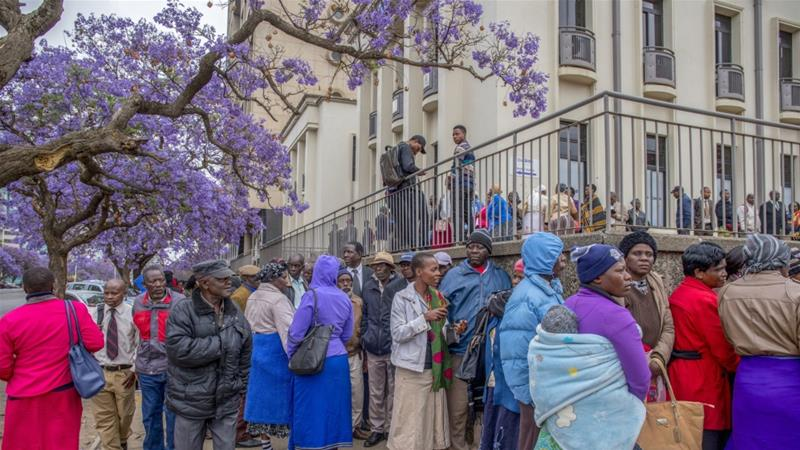 People queue to withdraw their pensions outside a branch of the Central Africa Building Society in Harare, Zimbabwe [File: Cynthia R Matonhodze/Bloomberg]