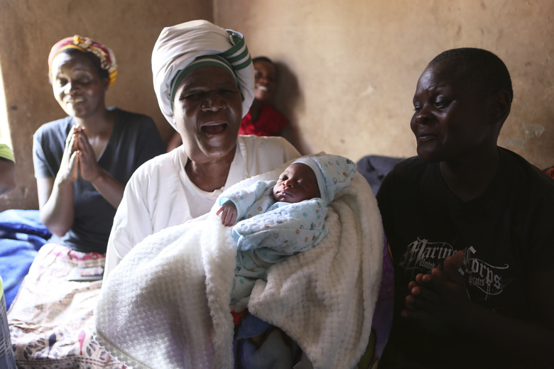 Esther Zinyoro Gwena holds one of the babies she has just delivered in her tiny apartment in the poor suburb of Mbare in Harare, Zimbabwe, Saturday, Nov. 16, 2019. Grandmother Esther Zinyoro Gwena claims to be guided by the holy spirit and has become a local hero, as the country's economic crisis forces closure of medical facilities, and mothers-to-be seek out untrained birth attendants.(AP Photo/Tsvangirayi Mukwazhi)