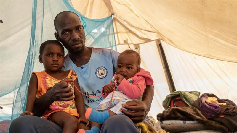 Kelvin Charamba with his daughters inside the tent the family has lived in for the past year [Tendai Marima/Al Jazeera]