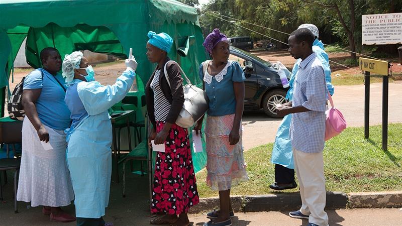 Health workers screen people visiting a public hospital in Harare, Zimbabwe [Tsvangirayi Mukwazhi/AP]