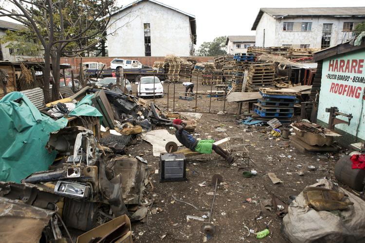 A man does exercises in a scrap yard, during lockdown due to the coronavirus, in Harare, Zimbabwe, Wednesday, April 8, 2020. (AP Photo/Tsvangirayi Mukwazhi)