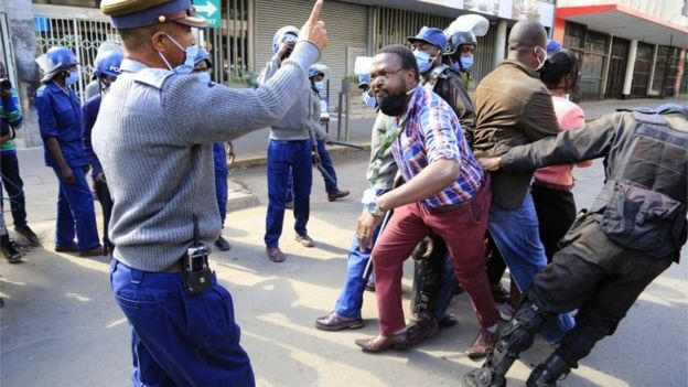 Police officers watch Movement For Democratic Change (MDC) Alliance youth leader Lovemore Chinoputsa is dragged by police officers outside the party headquarters in Harare, Zimbabwe, 05 June 2020