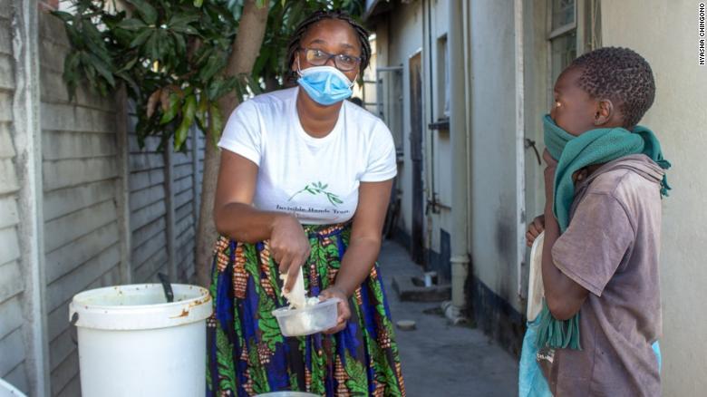 Samantha Murozoki serves food to a young child.