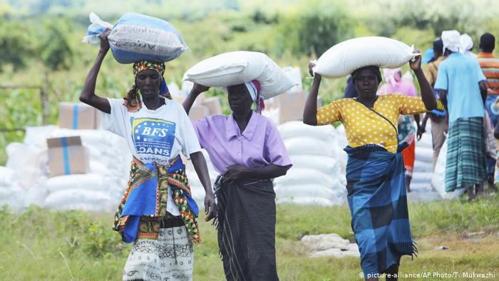 Women carry bags of corn on their heads