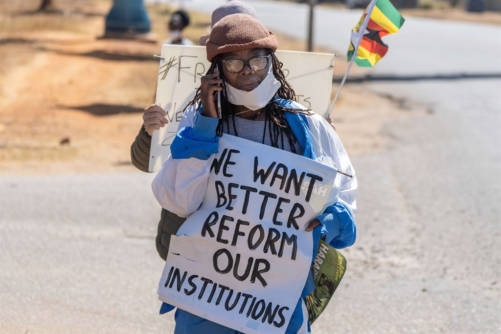Zimbabwean novelist Tsitsi Dangarembga holds a placard during an anti-corruption protest march along Borrowdale road, on July 31, 2020 in Harare.