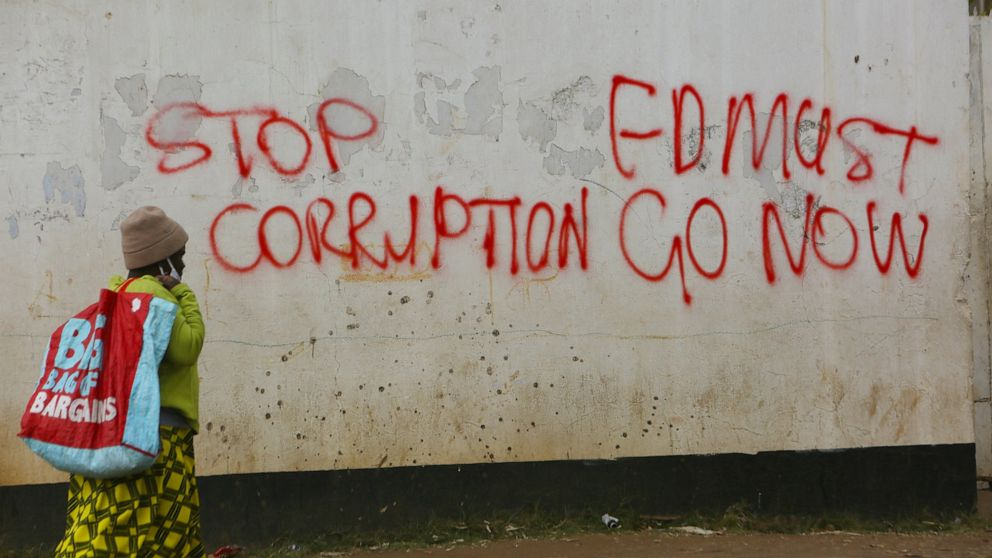 "A woman walks past a wall with graffiti calling on the government to stop corruption in this Monday, June, 15, 2020 photo. Unable to protest on the streets, some in Zimbabwe are calling themselves ""keyboard warriors"" as they take to graffiti and soci"