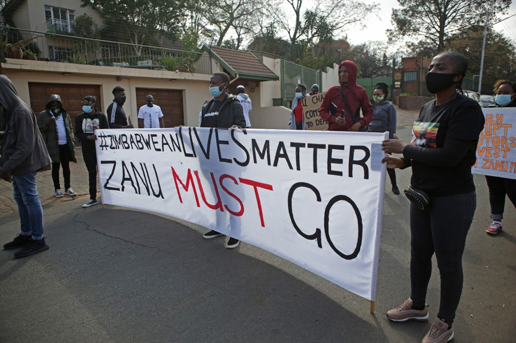 Protestors hold up plackards against the government of Zimbabwe's alleged state corruption, media freedom and the deteriorating economy outside the Zimbabwean Embassy in Pretoria on August 7, 2020.