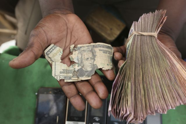 Currency dealers in Zimbabwe are repairing old US dollar notes