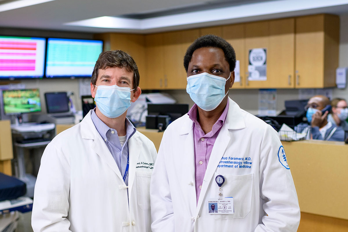 Josh and Mark Schattner posing in a medical office and wearing white coats and masks.